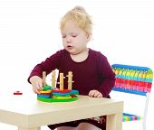 stock photo of montessori school  - Little girl sitting at a table playing puzzle Montessori Wednesday - JPG
