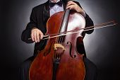 picture of cello  - Cellist playing classical music on cello on black background - JPG