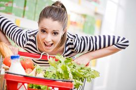 foto of grocery cart  - Woman gasping and pushing a full shopping cart at supermarket - JPG
