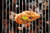 stock photo of flame-grilled  - Marinated grilled chicken on the flaming grill.