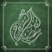 stock photo of ramadan calligraphy  - Arabic calligraphy text of Ramadan Kareem created by white chalk on green chalkboard background for islamic holy month of prayer - JPG