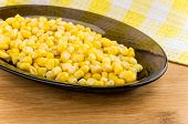 picture of sweet-corn  - Sweet canned corn in black oval glass dish on wooden table - JPG