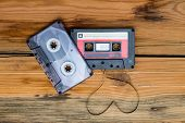 picture of heart sounds  - Vintage audio cassette with loose tape shaping one heart on a wooden background - JPG