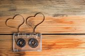 stock photo of heart sounds  - Vintage audio cassette with loose tape shaping two hearts on a wooden background - JPG