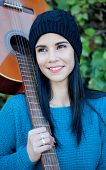 foto of guitarists  - Pretty guitarist with his guitar on his shoulder in the park - JPG