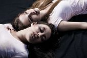 picture of bruises  - Two young beaten women with cuts and bruises lie down on the floor on black background - JPG