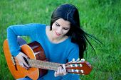 pic of guitarists  - Pretty guitarist playing the guitar sitting on the grass - JPG