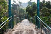 stock photo of suspension  - wooden suspension bridge across the river in rural thailand  - JPG