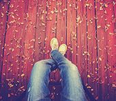 picture of loafers  - a pair of legs taken from overhead on a deck with leaves that have fallen toned with a retro vintage instagram filter app or action  - JPG