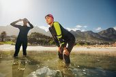foto of triathlon  - Determined sports persons standing in water getting ready for competition - JPG