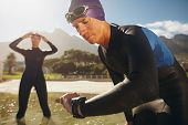 stock photo of watch  - Focused young man checking his watch while in wetsuit at the lake - JPG
