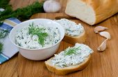 picture of baguette  - Slices of baguette with cottage cheese parsley garlic on a cutting board - JPG