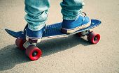 picture of snickers  - Young skateboarder in gumshoes and jeans standing on his skate - JPG