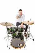 stock photo of drum-kit  - Handsome guy behind the drum kit on a white background in shirt and trousers - JPG