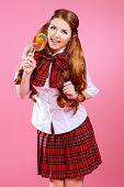 pic of up-skirt  - Pretty smiling teen girl in school plaid skirt and white blouse posing with lollipop over pink background - JPG