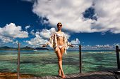 stock photo of jetties  - Woman with sarong on a tropical beach jetty at at Seychelles - JPG