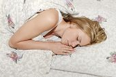 picture of sleeping beauty  - Beautiful young woman sleeping in bed in white top - JPG
