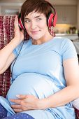 stock photo of bump  - Pregnant woman putting headphones over bump at home in the living room - JPG