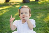 pic of teething baby  - Cute happy little baby girl in white dress smiling and scratching first teeth in park on green grass - JPG