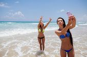 picture of two women taking cell phone  - two happy sexy girls selfie smartphone on beach - JPG