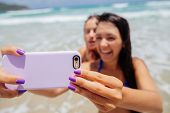 pic of two women taking cell phone  - two happy sexy girls selfie smartphone camer close up on beach - JPG