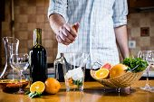 pic of sangria  - The man squeezes grapefruit juice in a decanter for making home sangria for home party - JPG