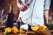foto of sangria  - The man squeezes grapefruit juice in a decanter for making home sangria for home party - JPG