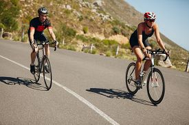 picture of triathlon  - Woman competing in the cycling leg of a triathlon with male competitor - JPG