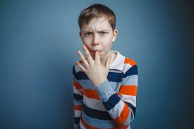 picture of finger-licking  - teenager boy of about ten European appearance Brown put his index finger in his mouth on a gray background - JPG
