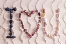 stock photo of agate  - I Love You romantic message in colorful pebbles on golden beach sand with a decorative pattern of undulating wavy lines using waterworn basalt agate and quartzite found in nature on the seashore - JPG