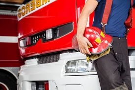 picture of firemen  - Midsection of young fireman holding red helmet while leaning on firetruck at station - JPG