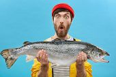 Indoor Shot Of Astonished Bearded Fisherman Dressed Casually Holding Huge Fish Looking At Camera Wit poster