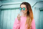 Young beautiful woman smoking weed on blurred background poster