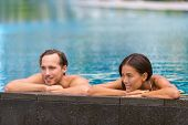Swimming pool wellness resort couple relaxing sunbathing in infinity luxury retreat pool in hotel. T poster