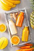 fruit and vegetable smoothies in glass jars, orange mango banana carrot pineapple poster