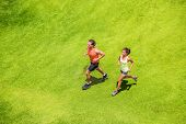 Runners running healthy people lifestyle. Active couple jogging together on grass park view from abo poster
