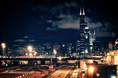 Chicago skyline cityscape at night featuring a train yard and urban bridge with a dramatic cloudy sk poster