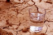 image of water shortage  - half full water over cracked earth representing danger of drought - JPG