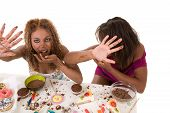 stock photo of bulimic  - Two attractive black girls trying to hide while eating lots of junkfood - JPG