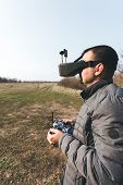 Fpv Drone Pilot In A Virtual Reality Helmet With A Remote Control From A Copter Flies In Aircraft Ou poster
