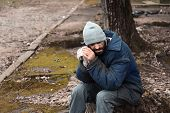 Poor Homeless Man Sitting On Stump Outdoors poster