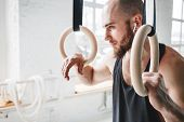 Male Bearded Athlete With Wireless Headphones Resting And Holding Gymnastics Rings At Light Gym. Fit poster