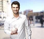 pic of piggy_bank  - portrait of a happy young man holding a piggy bank at the street - JPG