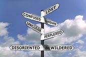 image of confused  - Concept image of a lost and confused signpost against a blue cloudy sky - JPG
