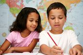 picture of mixed race  - Two young children at school writing with a pencil - JPG