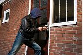 stock photo of illegal  - A burglar trying to get into a house by the backdoor - JPG