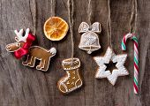 stock photo of cariboo  - Traditional gingerbread cookies hanging over wooden background - JPG
