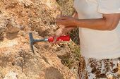 picture of paleontologist  - Senior woman geologist tap a rock formation with a hammer - JPG