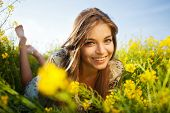 stock photo of wildflowers  - Cute happy girl lies among yellow wildflowers - JPG