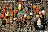 image of fishing bobber  - Colorful buoys and bobbers  hanging on a fishing net - JPG